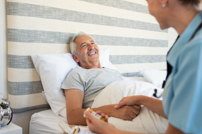 Cheerful senior man lying on bed receiving health care at home.