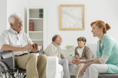 Elderly patients in nursing home talking with young nurse